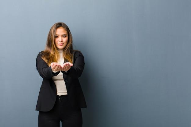 Donna di affari che sorride felicemente con lo sguardo amichevole, sicuro, positivo, offrendo e mostrando un oggetto o un concetto