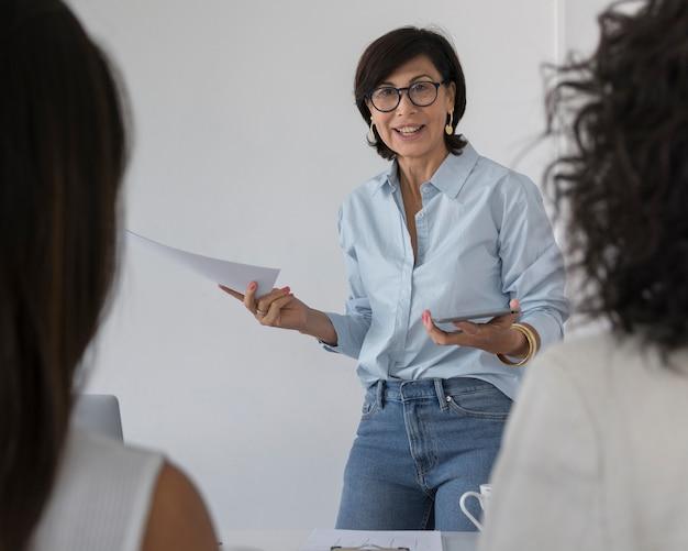 Donna di affari che spiega qualcosa ai suoi colleghi