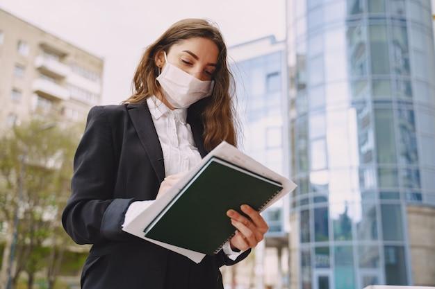 Donna di affari che sta all'aperto nell'edificio per uffici della città