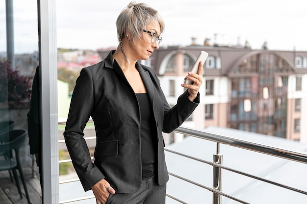 Donna di affari che sta e che esamina telefono