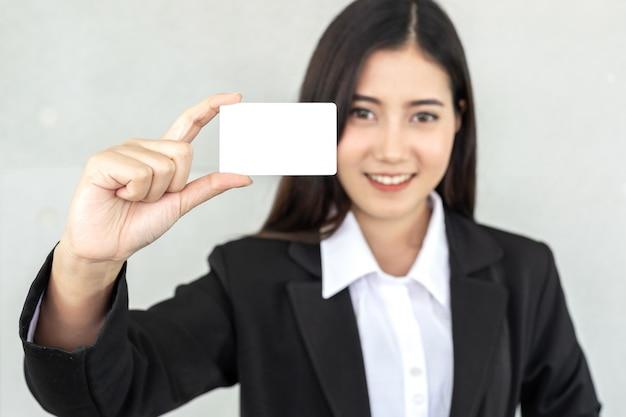 Donna di affari che tiene e che mostra biglietto da visita o carta di nome vuota