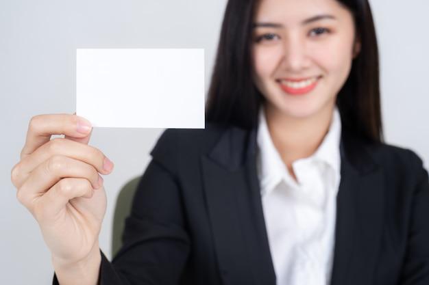 Donna di affari che tiene e che mostra biglietto da visita vuoto o carta di nome
