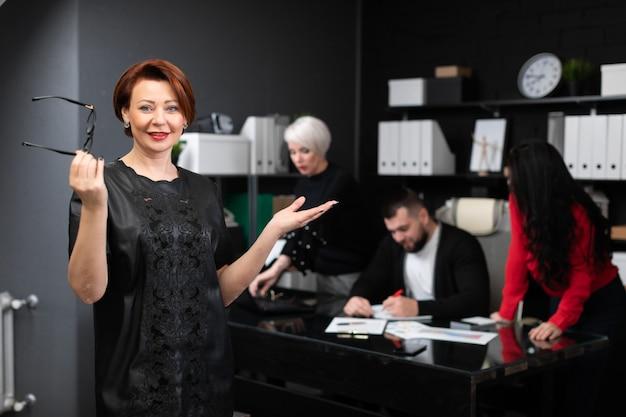 Donna di affari che tiene i vetri sopra degli impiegati che discutono progetto