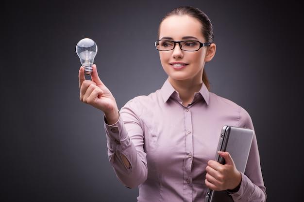 Donna di affari che tiene lampadina nel concetto di creatività