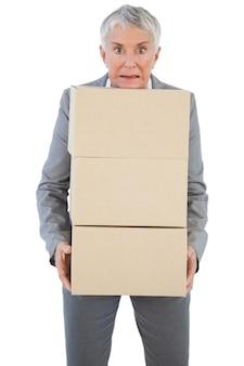 Donna di affari che tiene le scatole di cartone pesanti