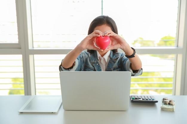 Donna di affari che tiene simbolo rosso del cuore sulla tavola con il computer