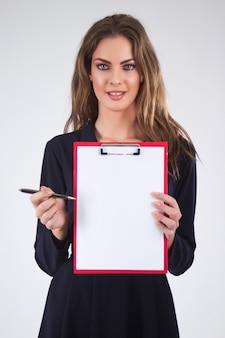 Donna di affari che tiene un appunti con la penna e lo spazio della copia, isolato