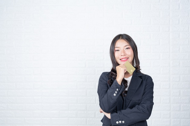 Donna di affari che tiene una carta di contanti separata, muro di mattoni bianchi fatto gesti con la lingua dei segni.