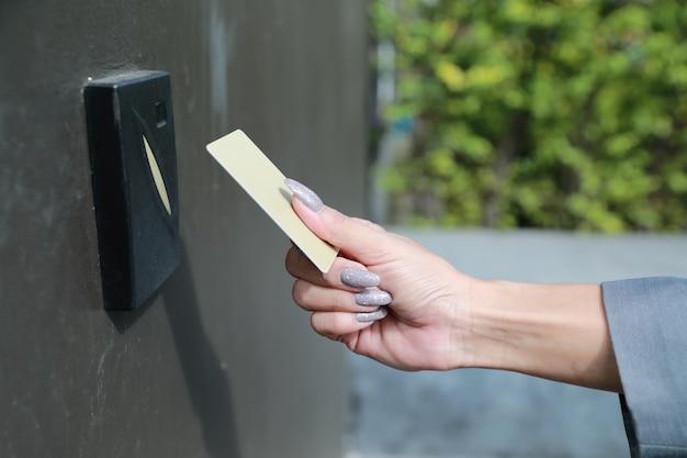 Donna di affari che usando la carta chiave elettronica per aprire l'ufficio