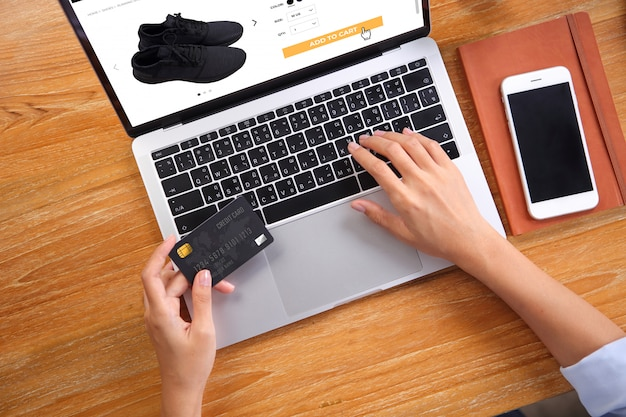 Donna di affari che usando la carta di credito per le scarpe da corsa nere dell'affare sul sito web di commercio elettronico tramite computer portatile con lo smartphone e taccuino sullo scrittorio di legno