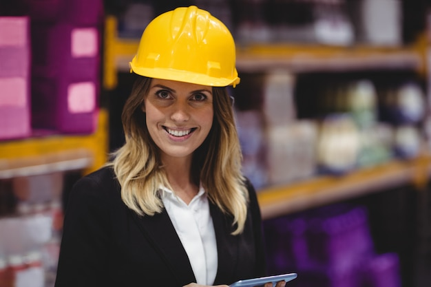 Donna di affari che utilizza compressa nel magazzino