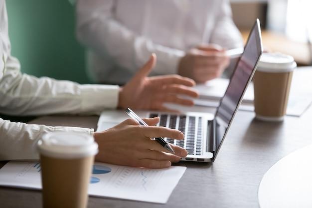 Donna di affari che utilizza computer portatile che presenta rapporto di progetto alla riunione d'affari, primo piano