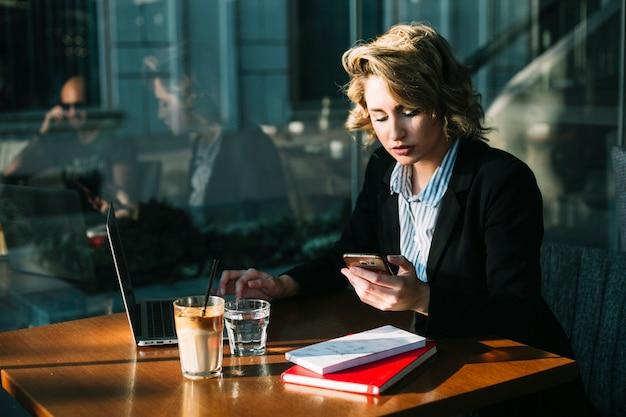 Donna di affari che utilizza computer portatile e cellulare nel ristorante