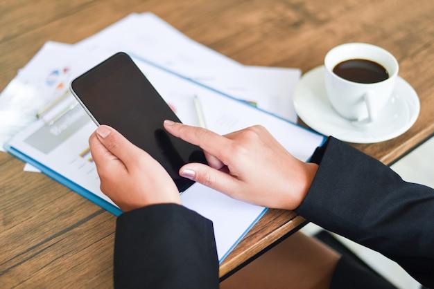 Donna di affari che utilizza smartphone e che lavora nell'ufficio con la relazione di attività sullo scrittorio della tavola con la tazza di caffè - le donne usa il telefono cellulare della tecnologia