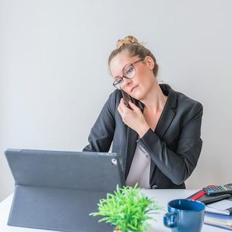 Donna di affari che utilizza smartphone mentre lavorando al computer portatile