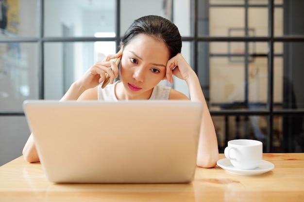Donna di affari che utilizza telefono e computer portatile nel lavoro