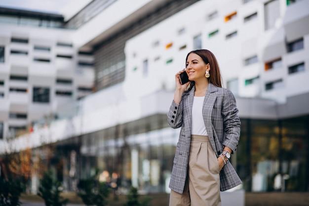 Donna di affari che utilizza telefono fuori nella via dall'edificio