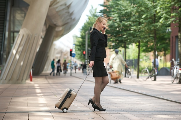 Donna di affari che viaggia con bagagli e telefono cellulare