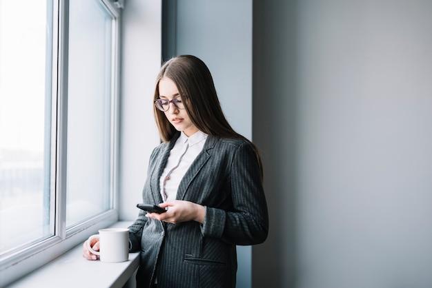 Donna di affari con caffè facendo uso dello smartphone alla finestra