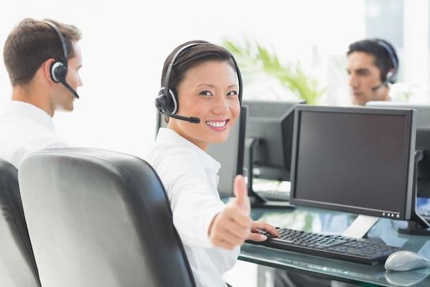 Donna di affari con i tumbs su che guarda l'obbiettivo mentre i suoi colleghi lavorano