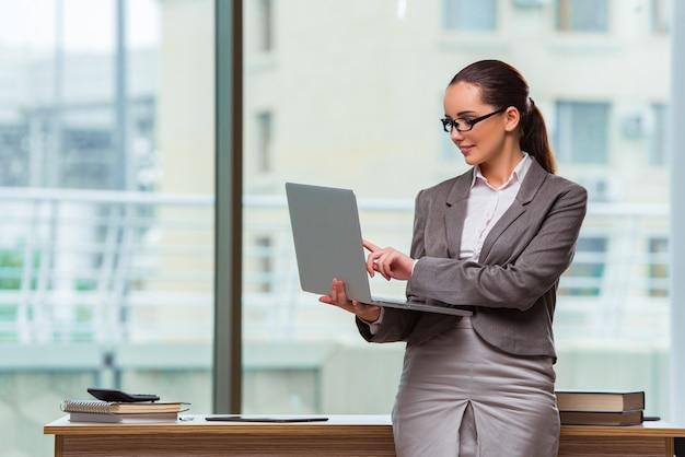 Donna di affari con il computer portatile nel concetto di affari