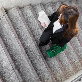 Donna di affari con il giornale e borsa che cammina sulle scale