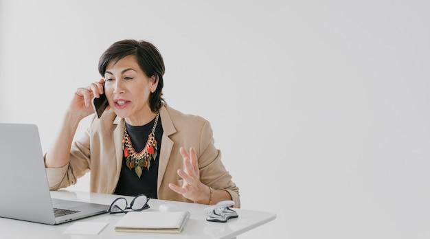 Donna di affari con la collana che parla sul telefono con copyspace