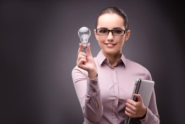 Donna di affari con la lampadina nel concetto di affari