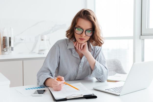 Donna di affari concentrata giovani in vetri e camicia a strisce che lavorano con le carte a casa