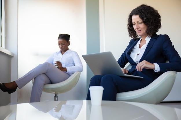 Donna di affari contenta che utilizza computer portatile nell'ufficio