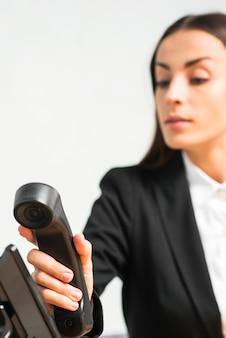 Donna di affari defocused che tiene ricevitore telefonico nero
