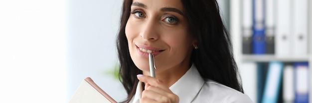 Donna di affari del brunette che propone penna sulle sue labbra
