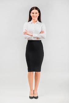 Donna di affari del brunette che si leva in piedi con le braccia attraversate
