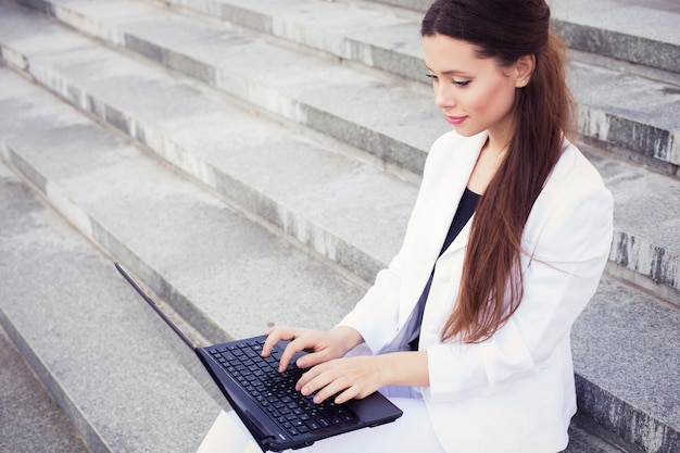 Donna di affari del brunette in vestito bianco con il taccuino in grembo, digitando, lavorando all'aperto. copia spazio