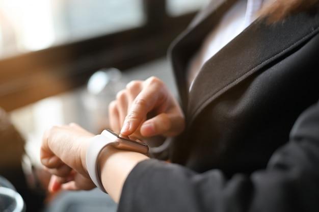 Donna di affari del primo piano che usando smartwatch.