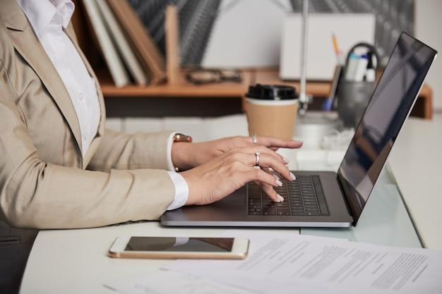 Donna di affari del raccolto che per mezzo del computer portatile