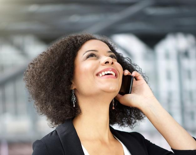 Donna di affari dell'afroamericano che comunica sul cellulare
