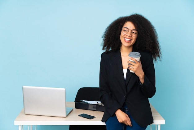 Donna di affari dell'afroamericano che lavora nel suo luogo di lavoro che osserva al lato