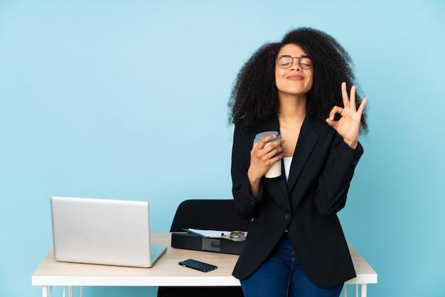 Donna di affari dell'afroamericano che lavora nel suo luogo di lavoro nella posa di zen