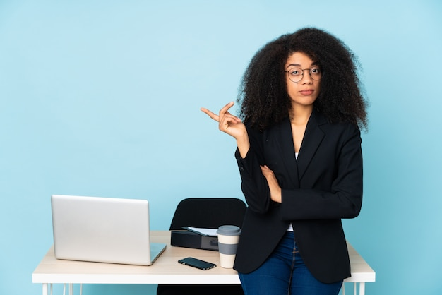Donna di affari dell'afroamericano che lavora nel suo posto di lavoro infelice per non capire qualcosa