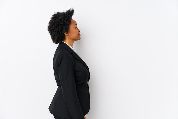 Donna di affari dell'afroamericano di mezza età contro una parete bianca che guarda a sinistra, posa laterale.