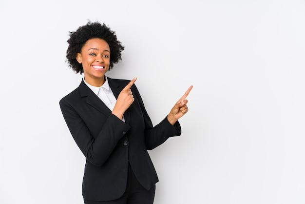 Donna di affari dell'afroamericano di mezza età contro una parete bianca che indica con gli indici uno spazio