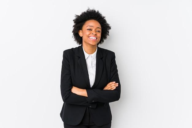 Donna di affari dell'afroamericano di mezza età contro una parete bianca che ride e che si diverte.