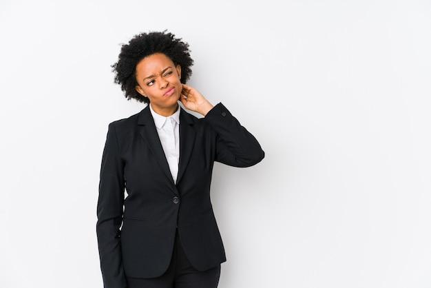 Donna di affari dell'afroamericano di mezza età contro una parete bianca che tocca parte posteriore della testa, pensando e facendo una scelta.