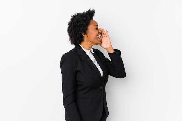 Donna di affari dell'afroamericano di mezza età contro una parete bianca isolata che grida e che tiene la bocca aperta vicino della palma.