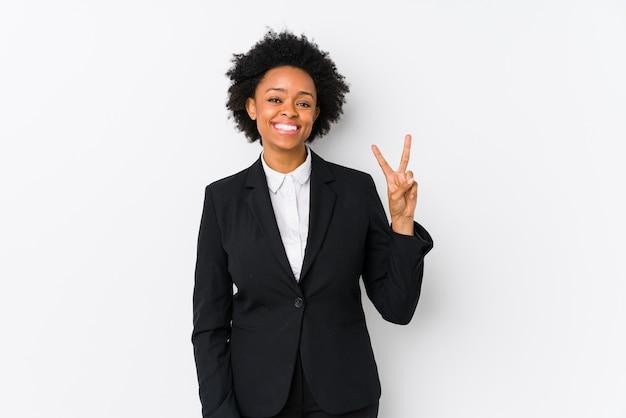 Donna di affari dell'afroamericano di mezza età contro una parete bianca isolata che mostra il segno di vittoria e che sorride ampiamente.