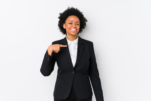 Donna di affari dell'afroamericano di mezza età contro una persona isolata bianca che indica a mano uno spazio della copia della camicia, fiero e sicuro