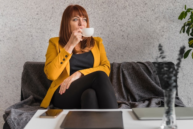 Donna di affari dell'angolo alto che gode del caffè