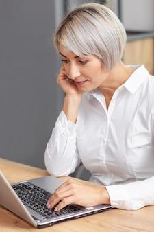 Donna di affari dell'angolo alto che lavora al computer portatile