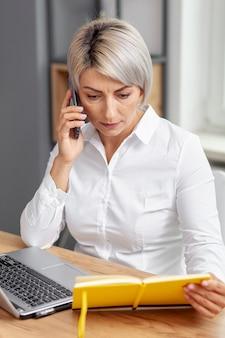 Donna di affari dell'angolo alto che parla sopra il telefono